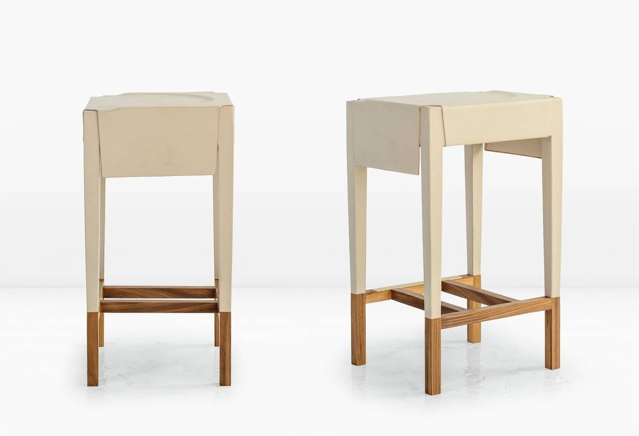 Utilizing a centuries old technique, water saturated leather hide is molded and stretched over a wood frame which is then exposed at the base to create the Cassius Barstool. An integral Brass footrest punctuates the base of the piece. Shown in Cream
