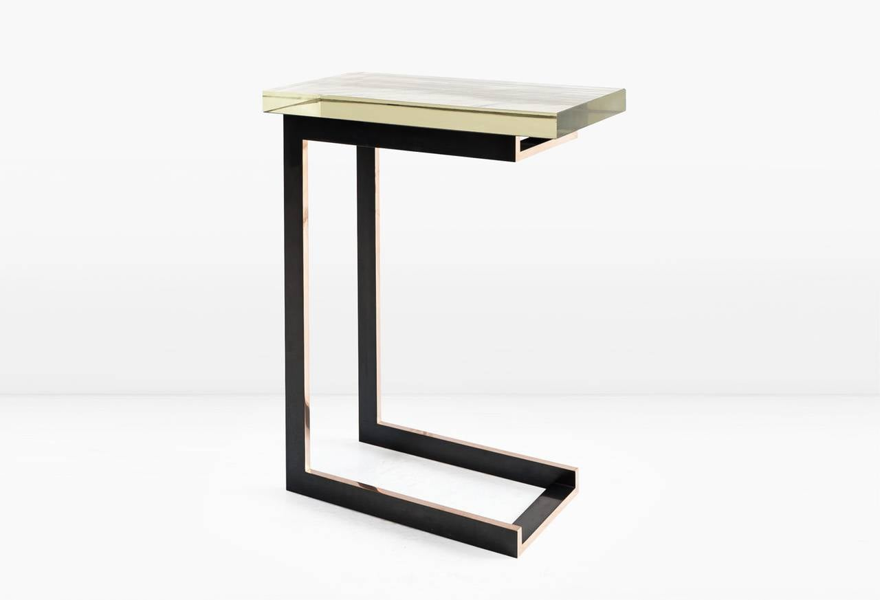 The Dempsey side table can easily assimilate into any room by virtue of both its elegant minimalism and its petite size. Shown with a 1 3/8 inch thick silvered Borosilicate glass top and deeply patinated, solid Silicon Bronze base which is polished