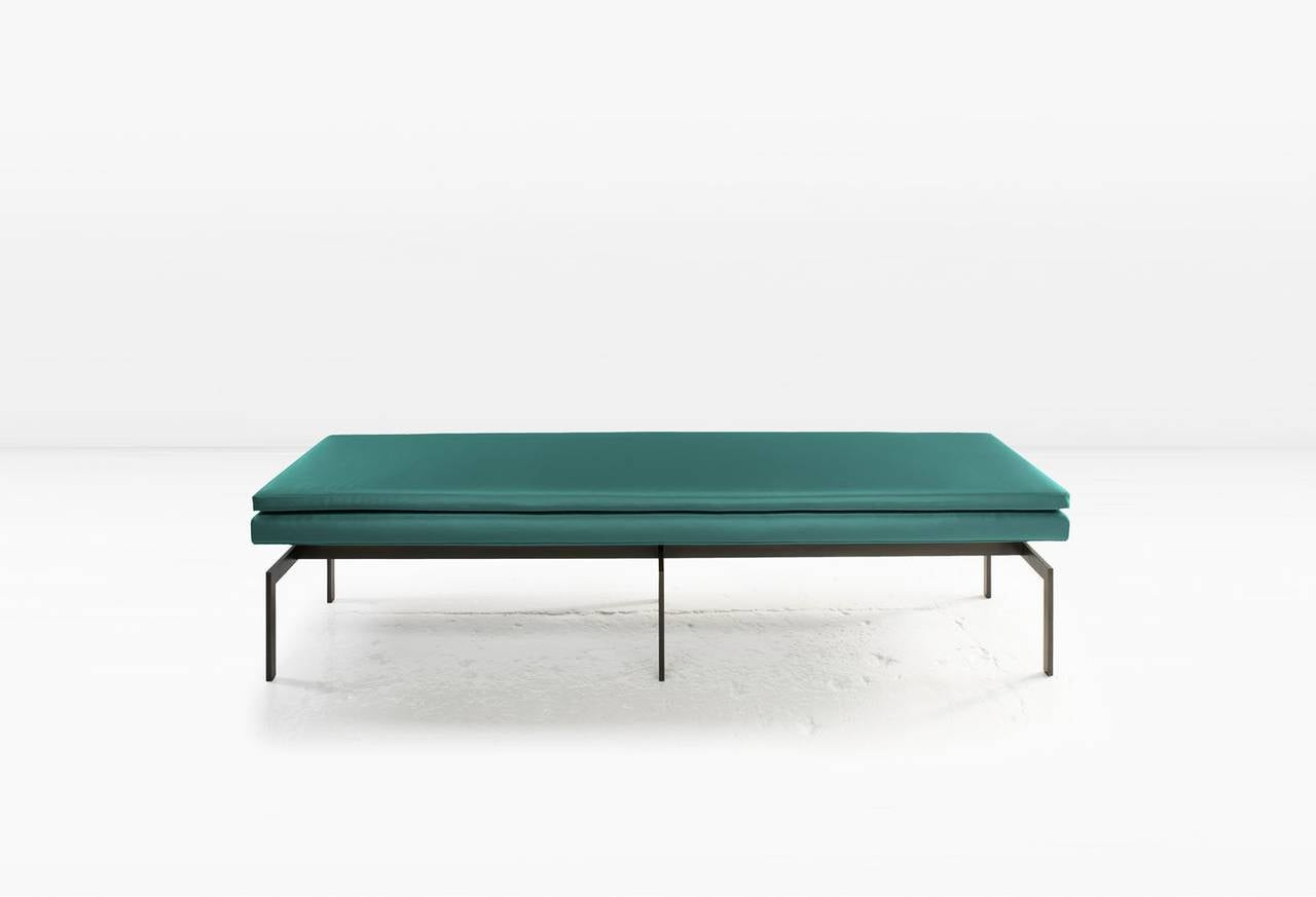 The cantilevered form of the Mancini bench stands out equally well as an entry piece or along one side of a dining table. Shown with a blackened steel base. It is also available in other metals. COM or COL (Customer's own fabric or leather. Fabric /