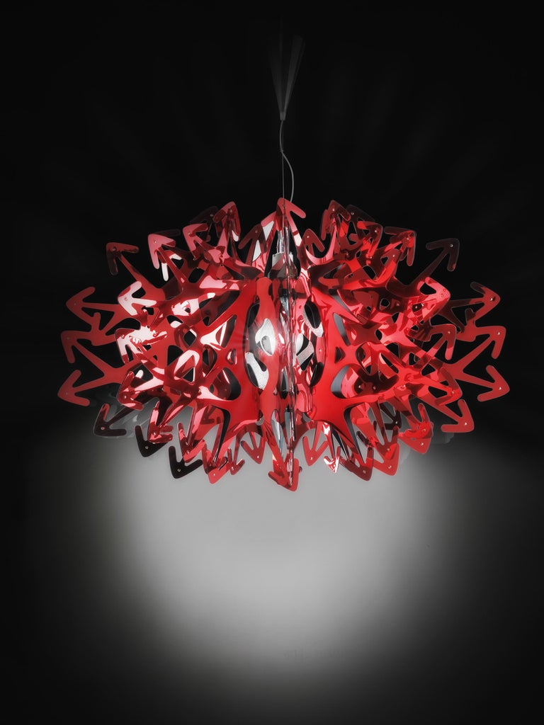 A meter-wide, opulent chandelier that brings sparkle to any interior. The layering of multiple, red metalized Steelflex® arrows make Devil mysterious and seductive, a tempting choice for spaces in need of personality and charisma. The lamp casts a
