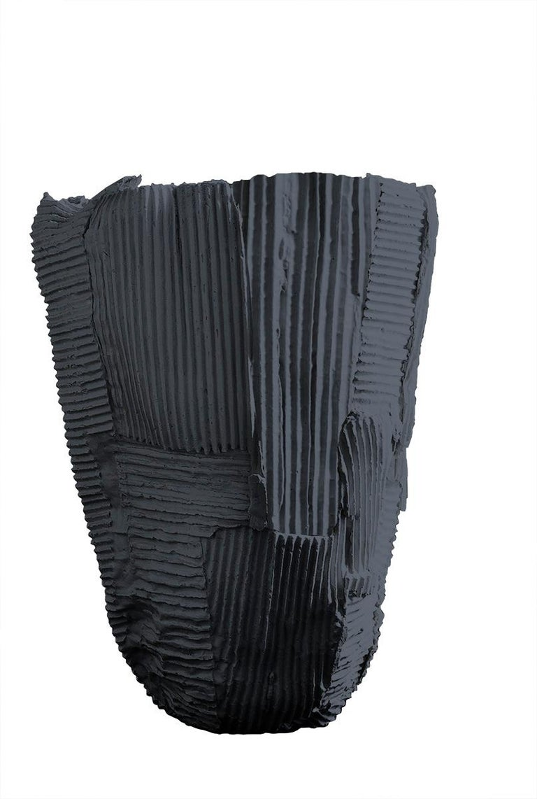 Sculptural yet subtle, this elegant tall vase will be a dynamic accent for a modern living or dining room. Reminiscent of a blooming flower, the tall silhouette with flared-out sides is entirely handcrafted of black paper clay, a compound that mixes