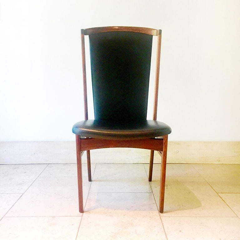 Substantial Danish faux black leather upholstered desk chair designed by Eric Buck (Buch) for Erik Christensen, 1960s.  Erik Buck was born in 1923 and like many of his Danish contemporaries, worked fabric and leather with grained woods. He is one