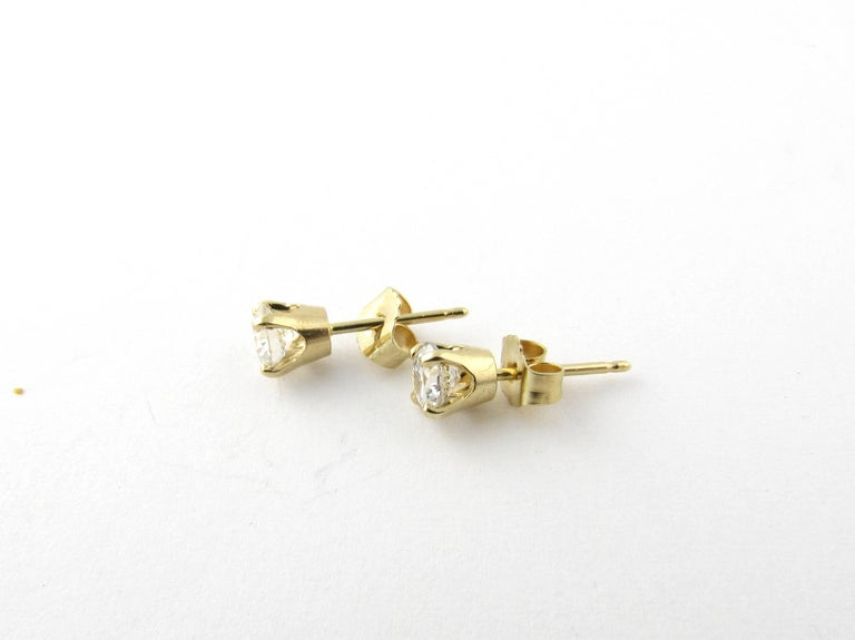 Vintage 14 Karat Yellow Gold Diamond Stud Earrings .60 ct. These classic stud earrings each feature one round brilliant cut diamond (.30 ct.) in a four prong yellow gold setting. Push back closures. Approximate total diamond weight: .60 ct. Diamond