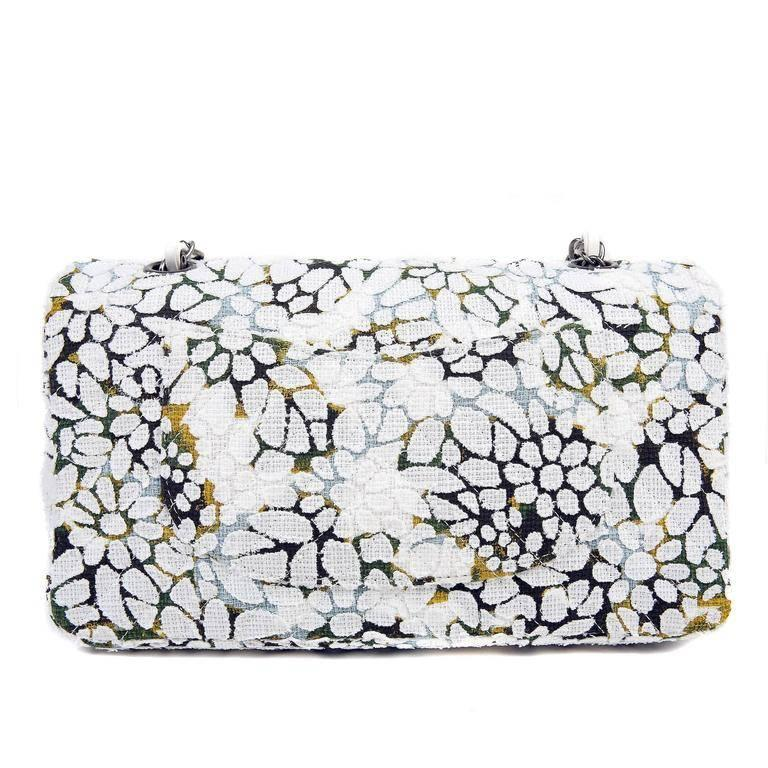 This Authentic Chanel Floral Tweed Classic Flap is in pristine condition. A stunning collectible from the Spring Summer 2015 Collection, this whimsical piece is perfect for any wardrobe. Medium sized double flap is covered in white laser cut tweed