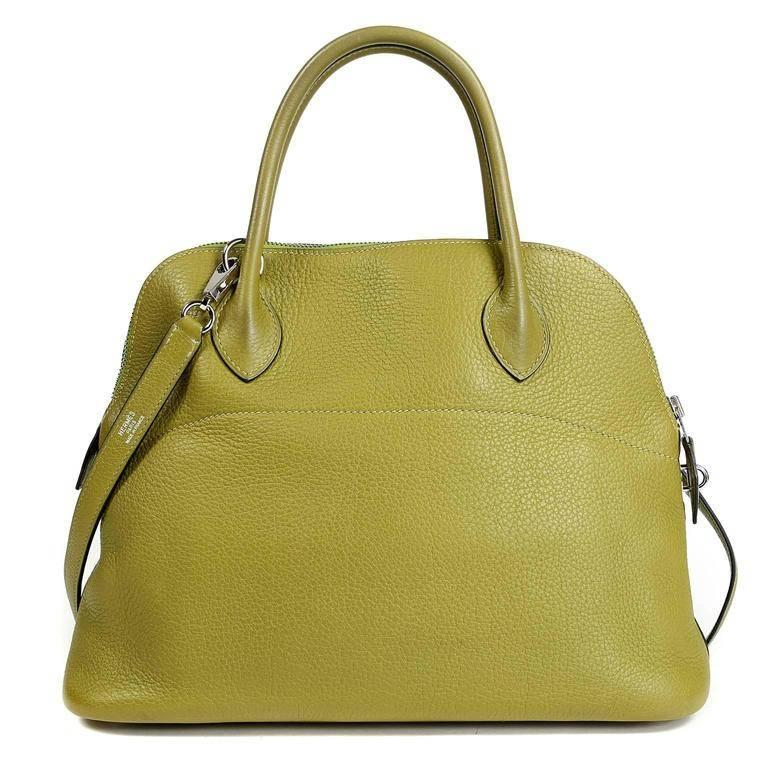 Hermes Vert Anis Clemence Leather 27 cm Bolide is in pristine condition, appearing never carried. The rounded top satchel is perfectly scaled and beautifully understated; a must have for any comprehensive wardrobe. Hermes bags are hand stitched by