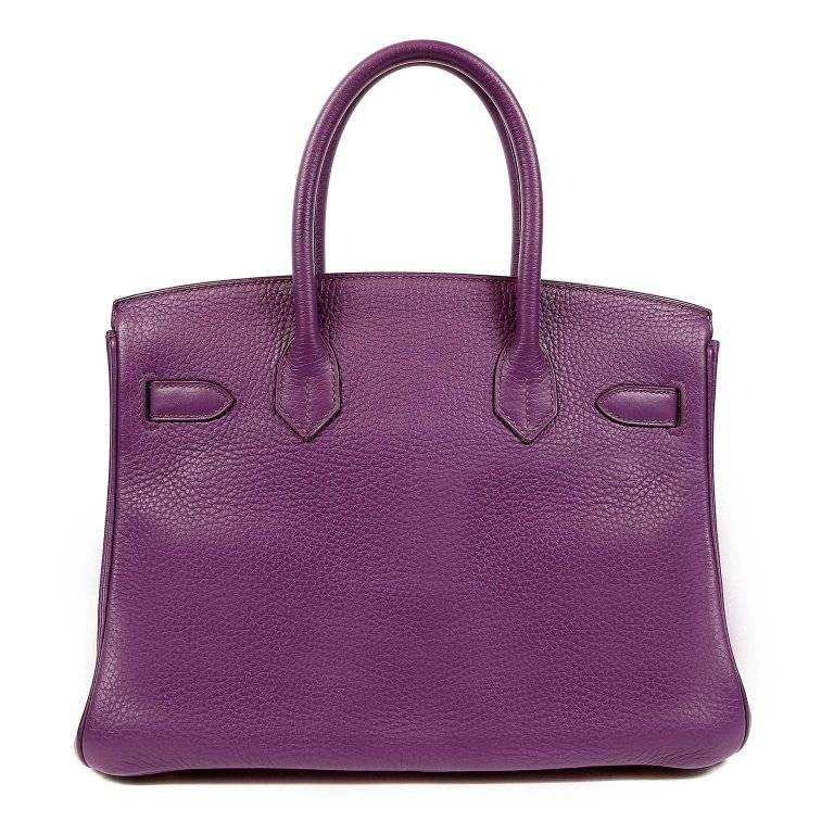 This authentic Hermes Ultra Violet Togo 30 cm Birkin is in pristine condition. The protective plastic is still intact on most of the hardware. Hand stitched by skilled craftsmen, wait lists of a year or more are not uncommon for the Hermes Birkin.