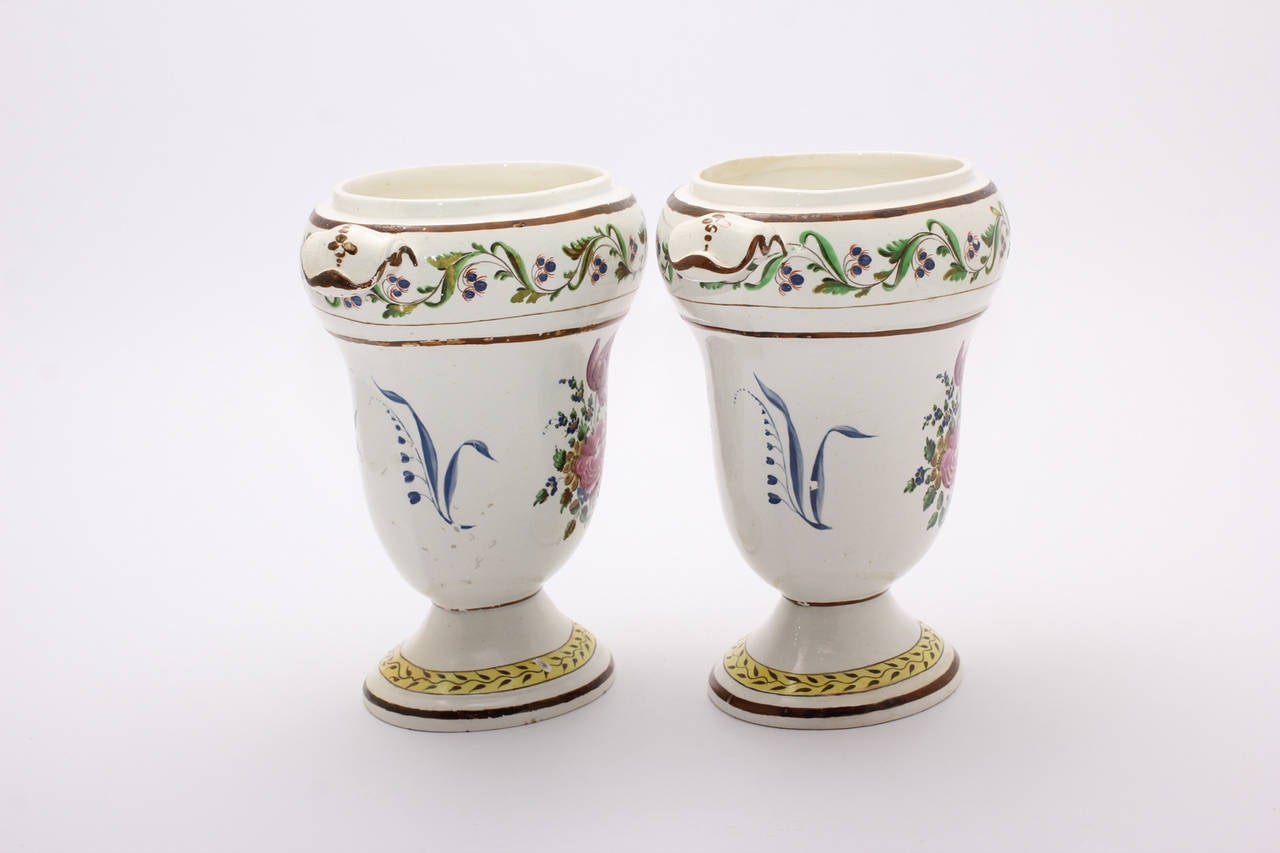 Pair of creamware pottery vases, of oval form with short spreading foot, painted with flower sprigs, the lower border with brown vine on yellow ground, the upper with scrolling cornflower, within brown line borders. 