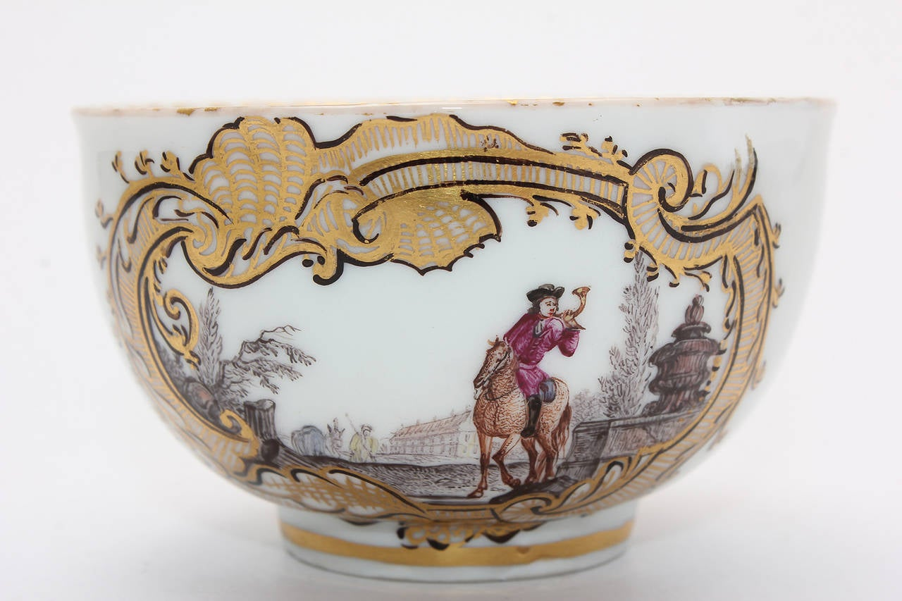 Meissen tea bowl and saucer finely painted with equestrian scenes in an unusual muted palette, including a humorous scene of a rider coming across a bather, within ornate gilt Rococo cartouche having black outlines.