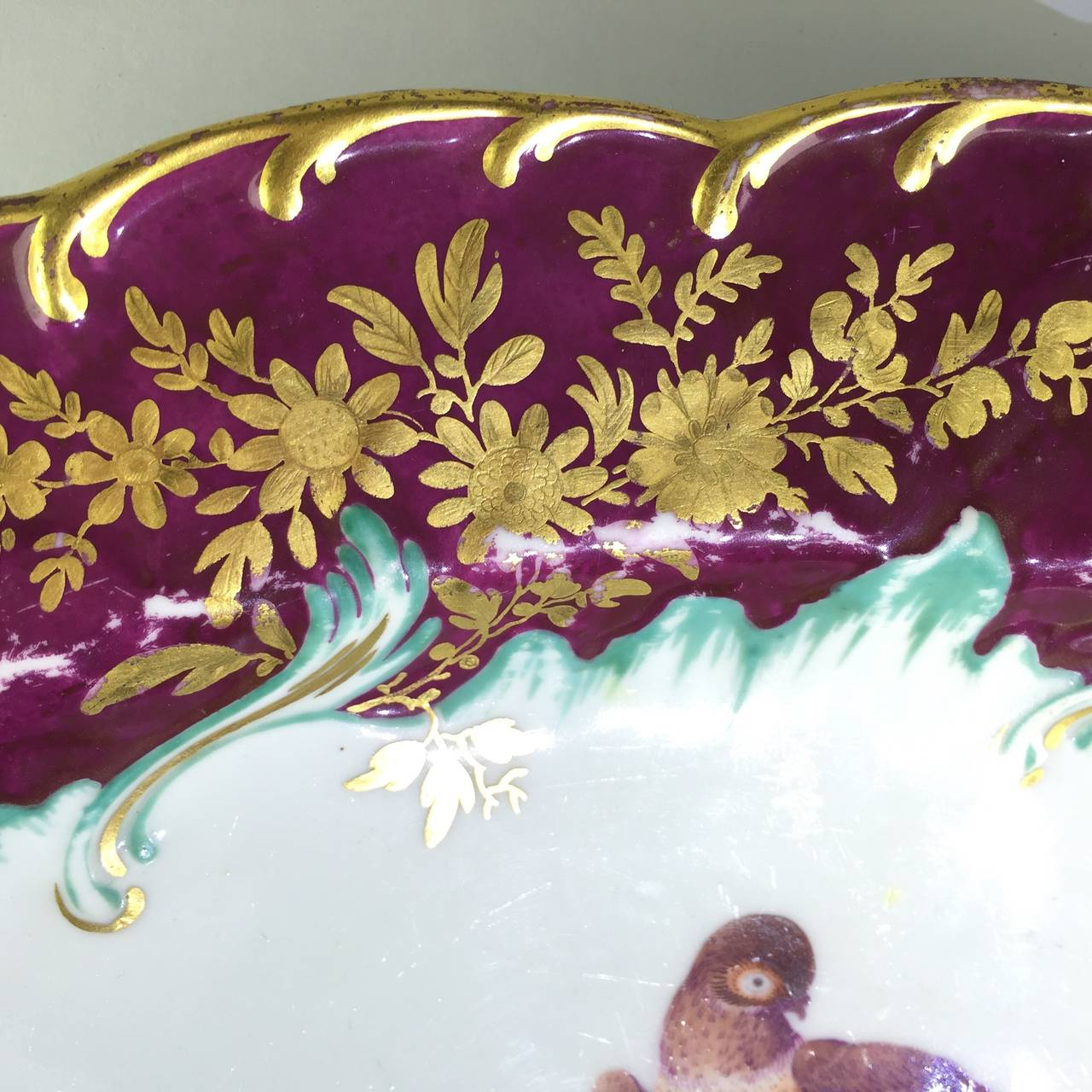 Chelsea Gold Anchor oval dish with pinecone moulded border and scroll moulded rim, richly gilded with tooled flower groups on a claret ground, the well feather moulded and picked out in turquoise, with a central colourful exotic bird perched on a