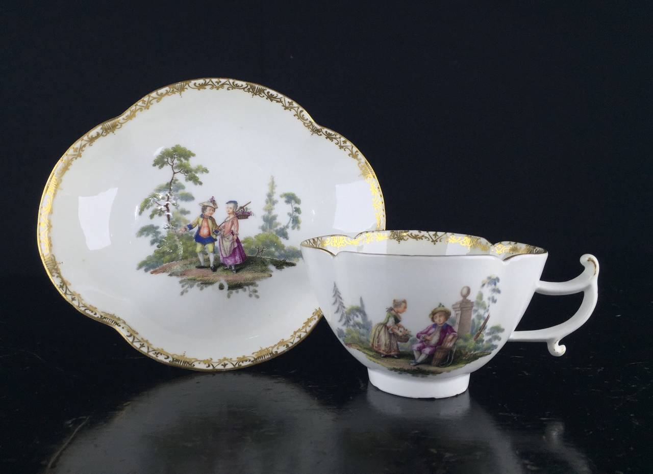 Rare Meissen quatrefoil shape cup and saucer with elegant handle, finely painted with children in landscapes, one side of the cup with a boy showing a girl his empty grape basket, while on the other side he plays a pipe to her, his basket being full