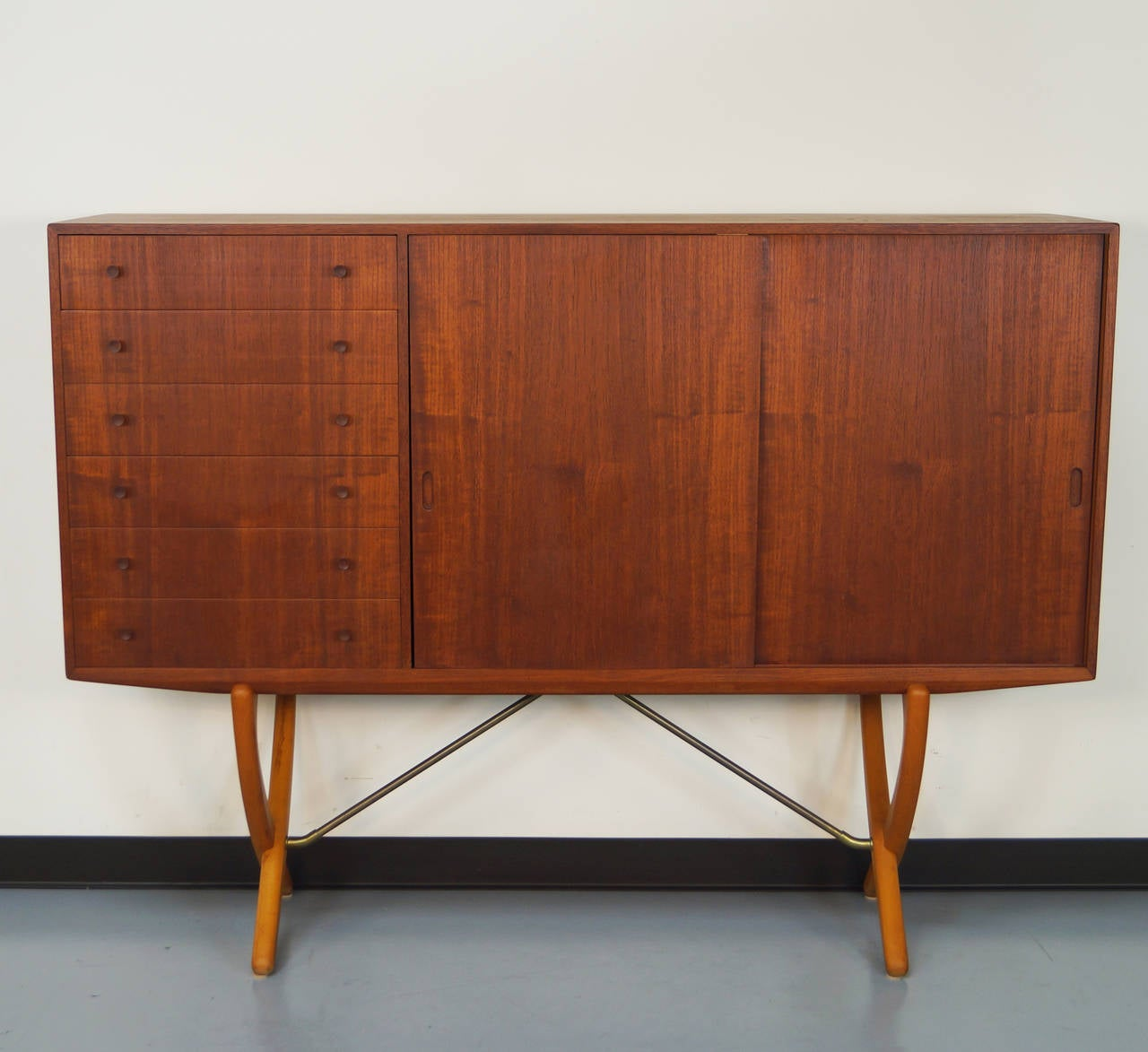Danish modern teak credenza designed by Hans J. Wegner for Carl Hansen. Features six dovetail drawers and two sliding doors concealing three adjustable shelves and shallow drawers/trays. This piece is in excellent vintage condition.