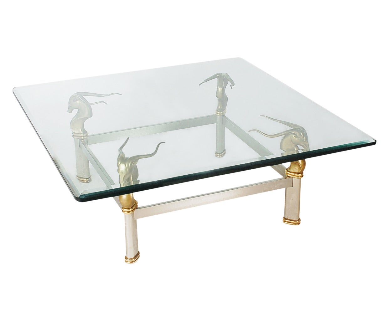 A chic looking two-tone coffee table with a Gazelle head motif. It features brushed stainless steel and solid brass frame, with a thick heavy glass top.