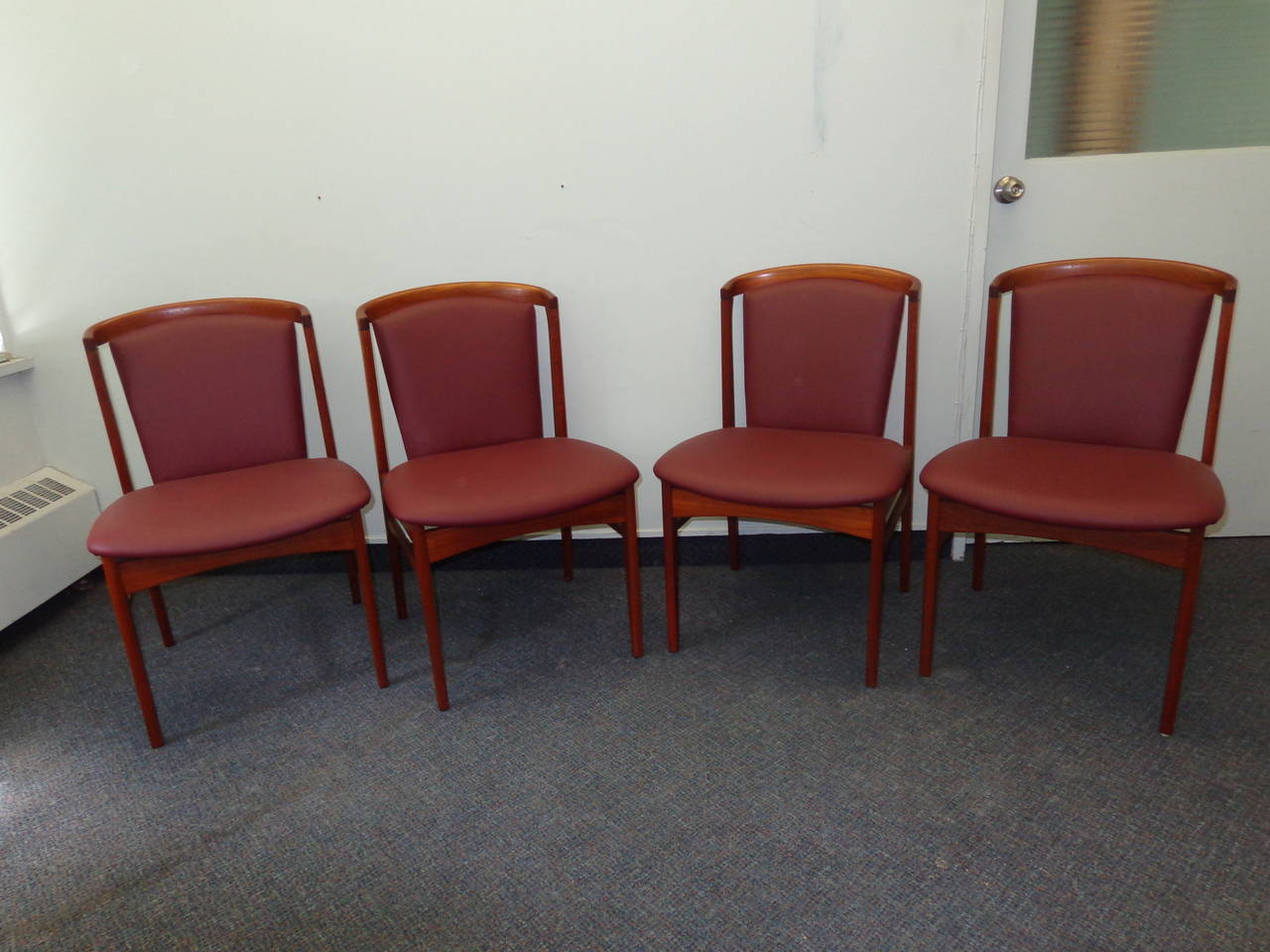 Teak dining chairs by Erik Buch reupholstered in leather.