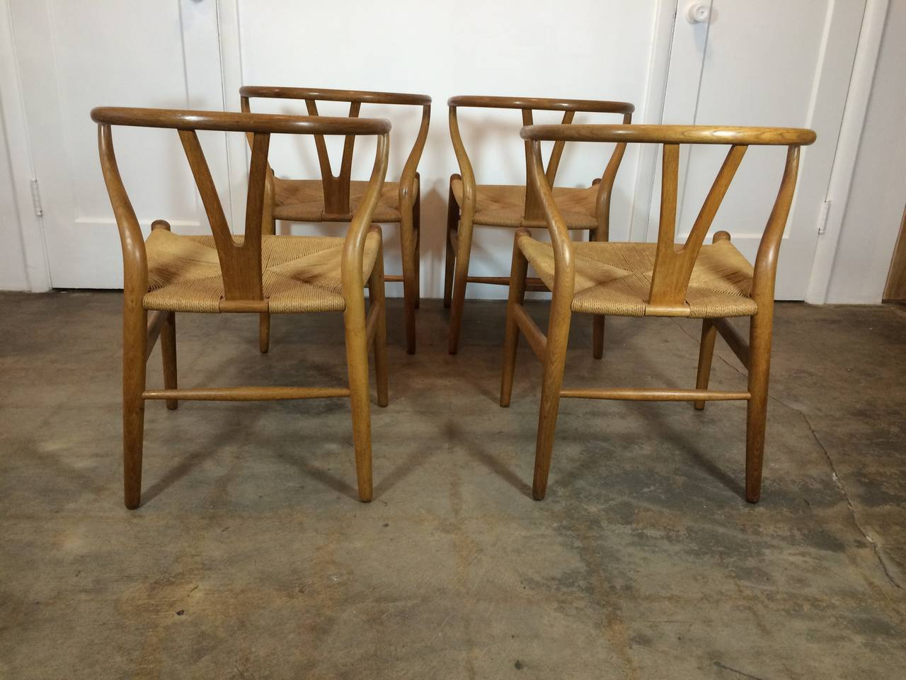 Early production wishbone chairs in original finish. Shipping tags to US included. Oak and paper cord construction, perfect for a dining room set.