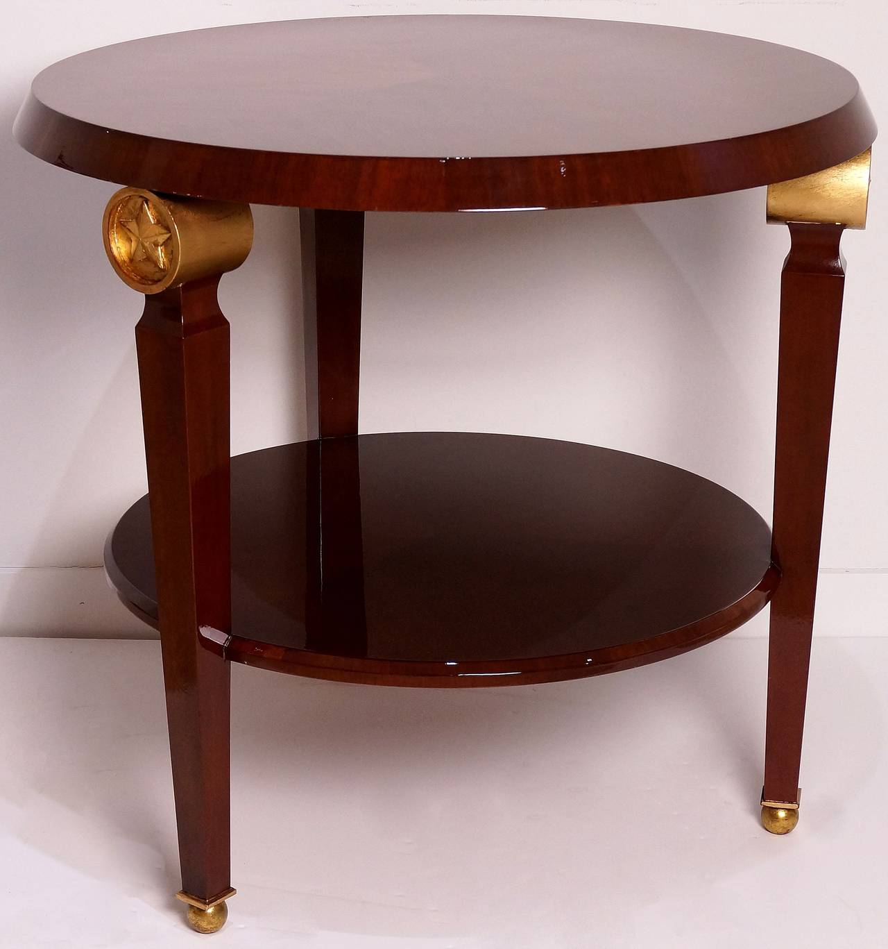 This two-tiered center-table is in the style of Maison Jansen, with its gold-finished star medallions,  mahogany wood veneers and solids this piece has an overtone of French Art Deco and French Empire in the taste moderne.