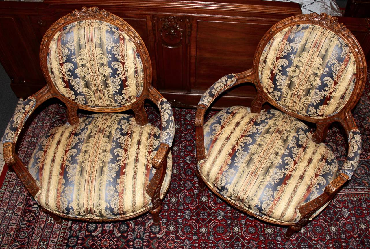 This pair of French armchairs is made in the Louis XVI style.  The chairs are carved with a design in line with this style.  The pair has been reupholstered in a neutral fabric which has tones of blue and red running through it.