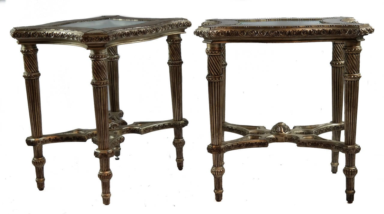 Pair of side tables, silver-leafed, with carved reeded legs and beveled edge glass insert top.