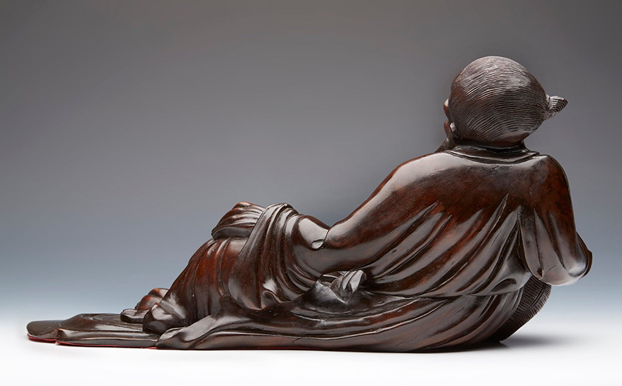 An antique lacquered hard wood figure of a reclining immortal. He is resting on a basket and with a miniature fisherman presenting him a large fish. The figures are disproportionate to each other and the carver possibly is reflecting on the