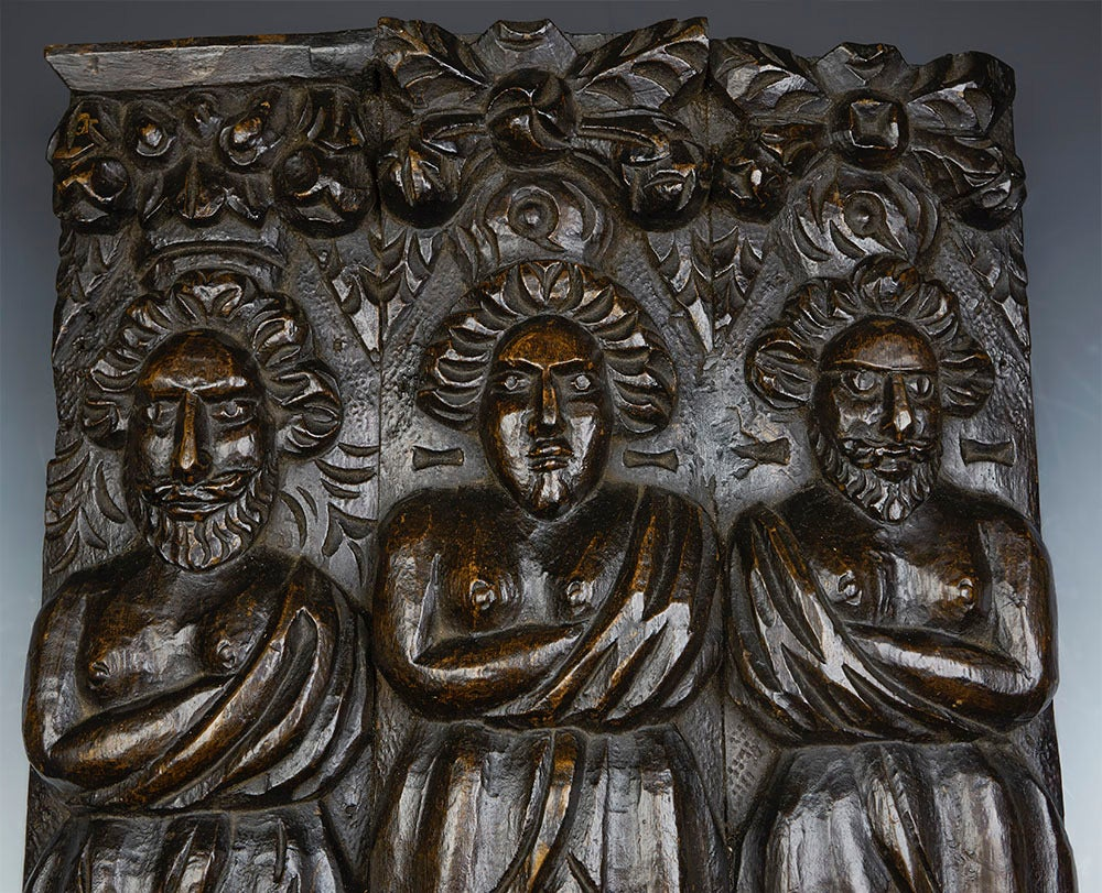 A carved architectural wooden panel mounted on a pedestal base dating from the 17th century. The hard wood panel is carved in deep relief from three pieces of wood. The three figures could possibly be saints, stood beneath floral garlands. The panel