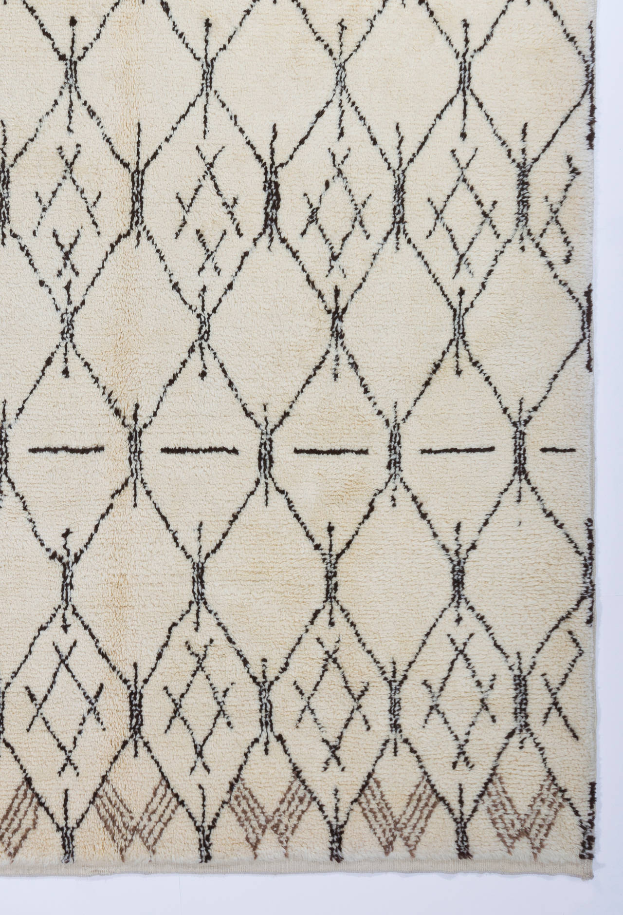 The design of this modern hand-knotted rug is inspired from vintage Moroccan rugs and it is woven in a Turkish village by three highly skilful adult female weavers who have inherited the tradition of rug making from their mothers. 