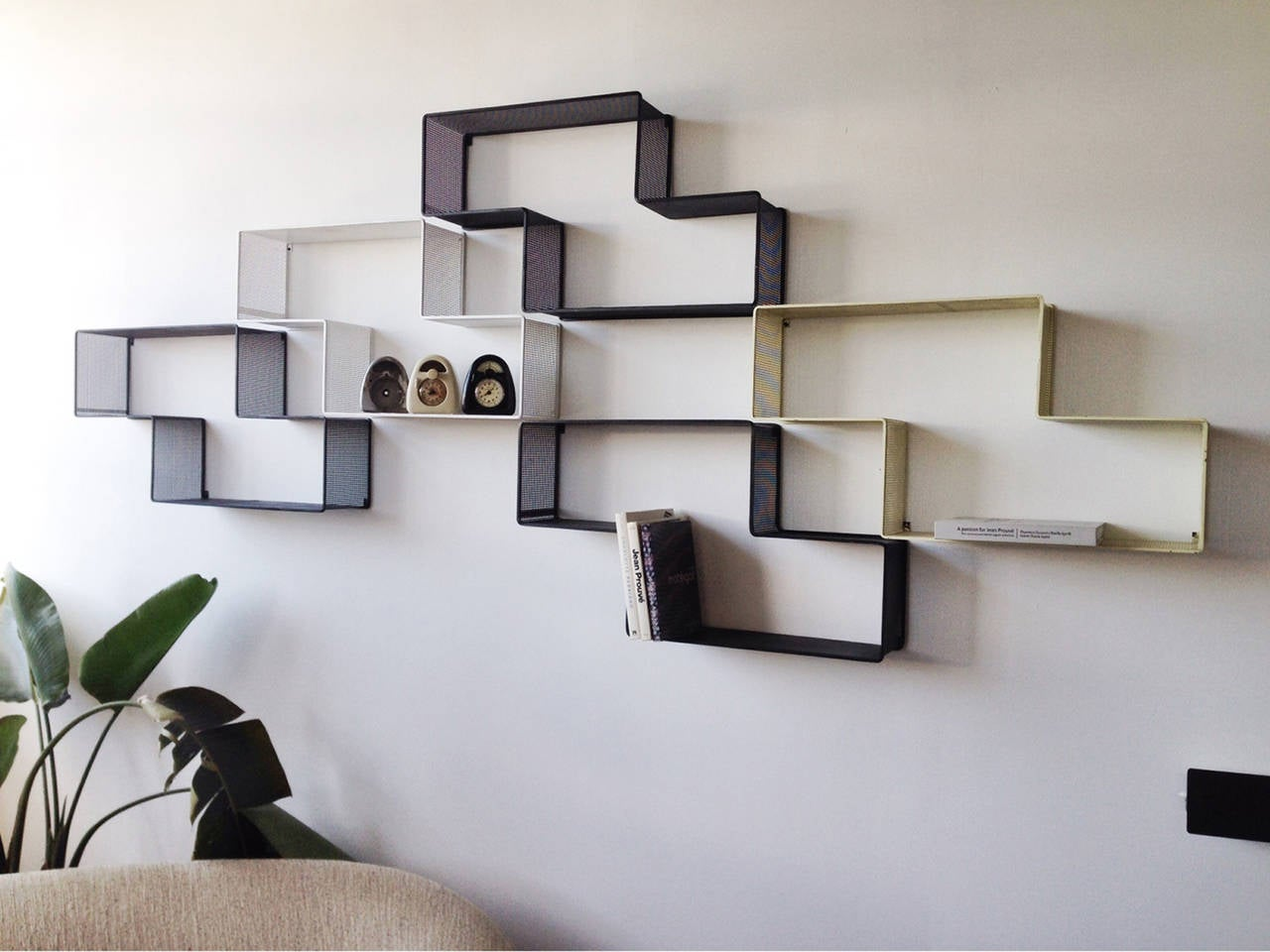 Set of five reconfigurable, perforated steel shelves in black, white, and pale yellow by Hungarian/French designer and material artist Mathieu Matégot. Manufactured by Atelier Matégot, France.
