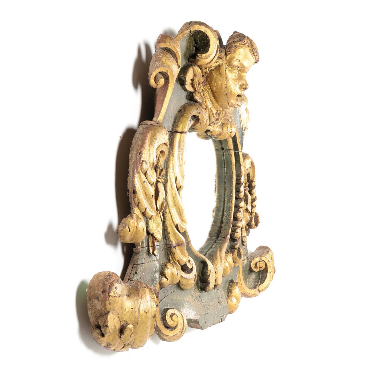 An Italian Baroque over-mantel mirror frame with cherubic figure, Circa 1680-1720. Impressive size with gilt-and-green decorative carvings. Extremely rare and in fantastic original condition with beautiful wear, patina, and age marks consistent with
