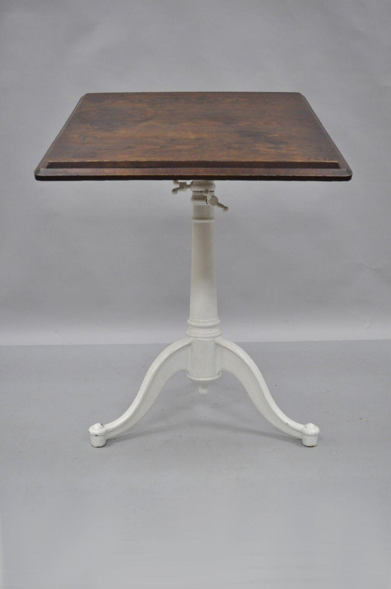 Antique cast iron and wood small drafting work table by Eugene Dietzgen. Item features cast iron tripod base, solid wood top, original tag, adjustable height and tilt, quality American craftsmanship. Later added white painted finish to base, circa