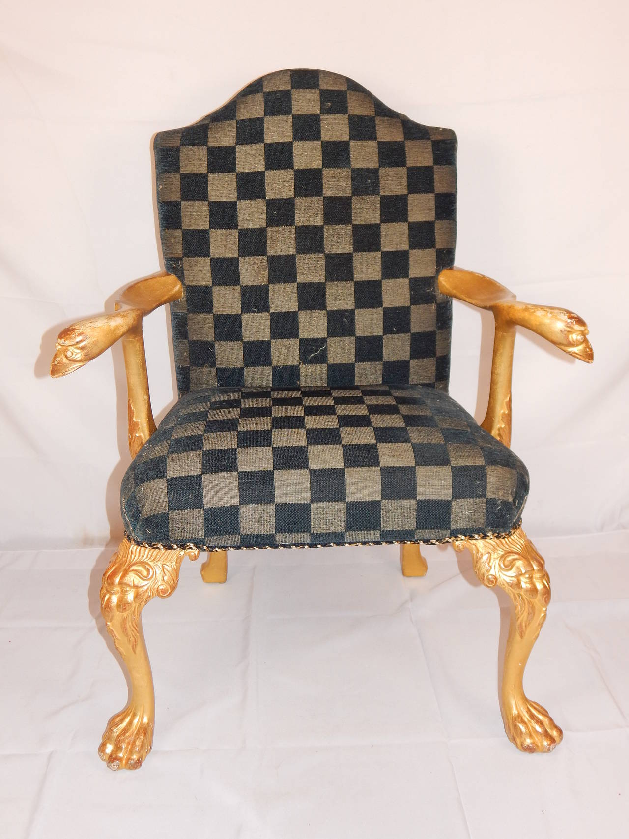 An exceptional set of eight George I style gilt wood dining chairs, comprising of two armchairs and six sides, each with arched padded back and seat, the armchairs with out-scrolled arms, terminating in carved bird's heads, on lion head carved