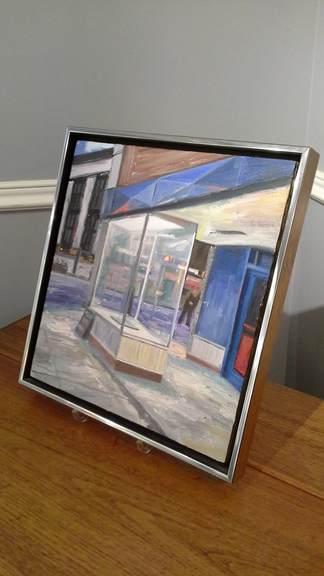 """Oil Painting on Board by Brian Kipping Store Front in Vancouver, BC. The painting is titled """"Display Case On Cambie"""". Signed on Verso, and printed in Black Marker, dated 2007, Famed in modern chrome frame sold by """"Wallack's Gallery in"""