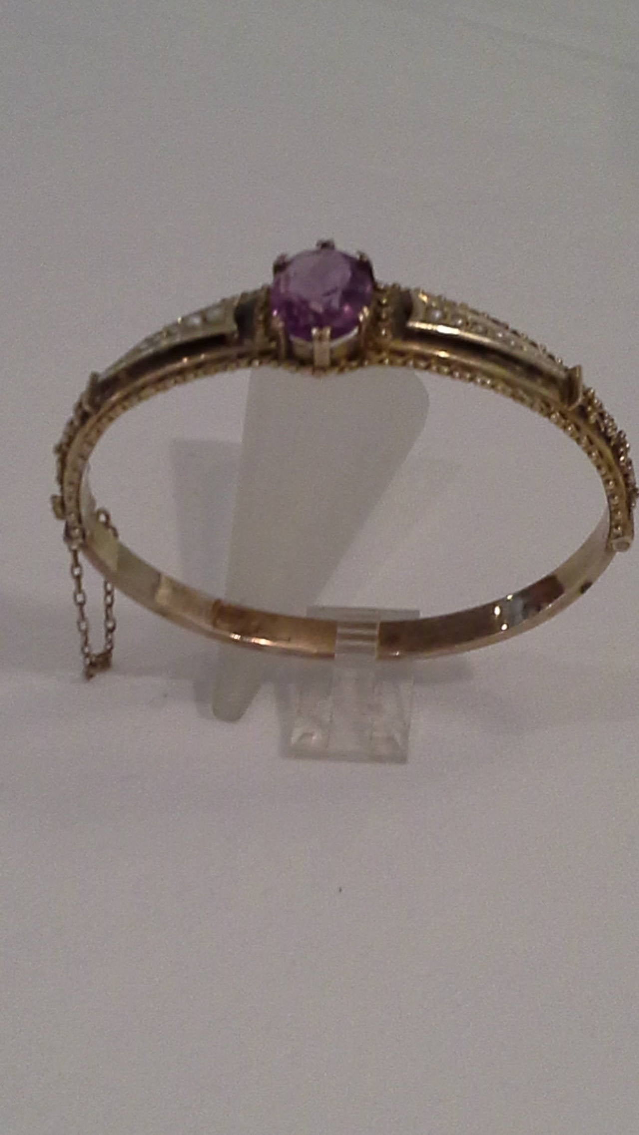 Victorian Amethyst and Seed Pearl Bangle or Bracelet, 9k Gold, Stamped .375, The bracelet has a faceted Amethyst center stone with five graduated seed pearls on either side, gold bead accents on both sides, with floral beads and has a safety chain.