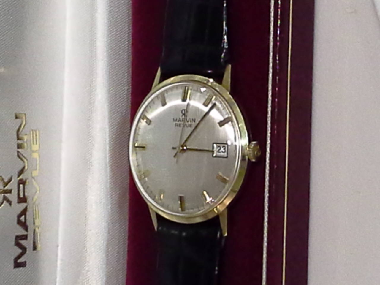 Marvin Revue Day/Date Gold Wristwatch With Original Bracelet/Buckle & In Original Box, The watch is stamped 0.375 10K on the back case, Manual wind, Original crown with double RR logo and baton markers. The watch is in fine working order. The