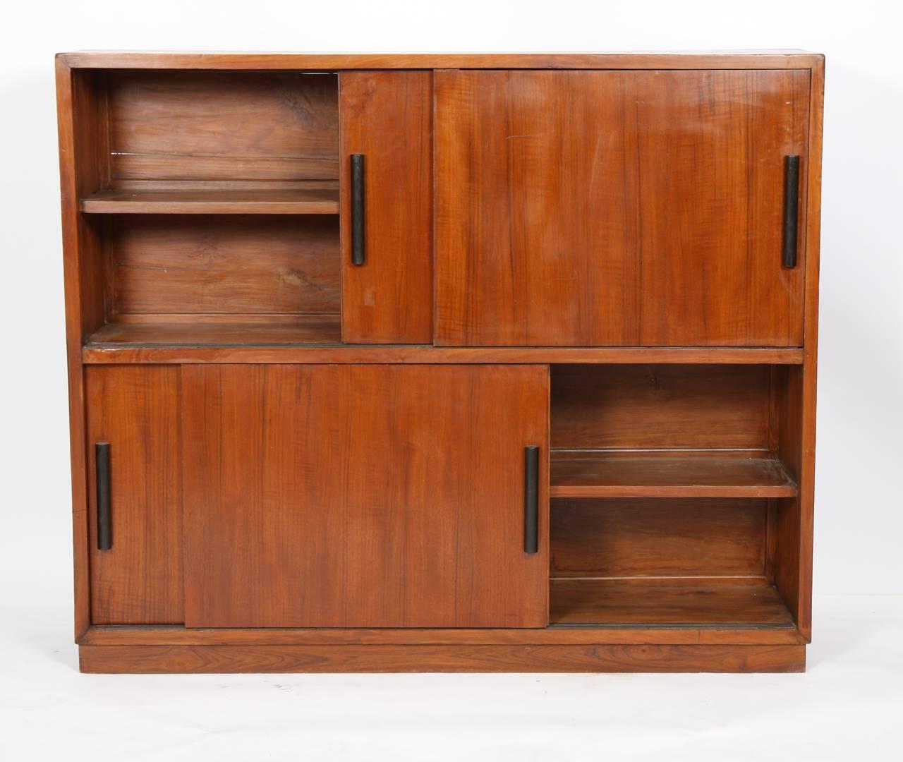 """""""Pierre Jeanneret (1896-1967).  Exceptionnel et très rare meuble de rangement de la caféteria"""""""" en teck massif et placage de teck.  Ouvrant par quatre portes en contreplaqué, coulissants sur rail à prise rouleaux en bois teinté"""