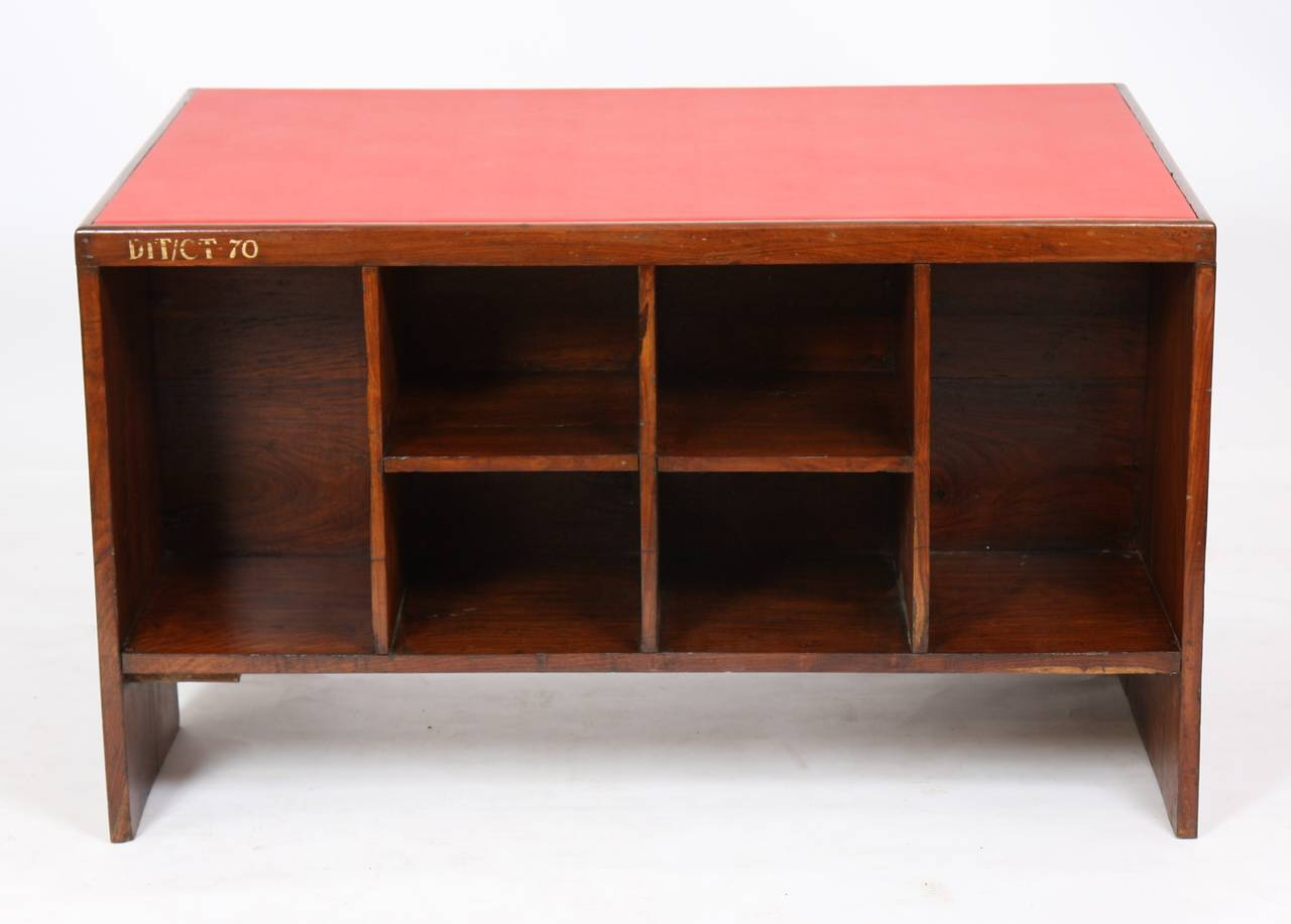 Pierre Jeanneret (1896-1967) Solid teak office desk (office table).  Rectangular framed top covered with red moleskin. Fixed on one side on a panel forming the left side casing base with opening for a drawer and storage rack and the other side