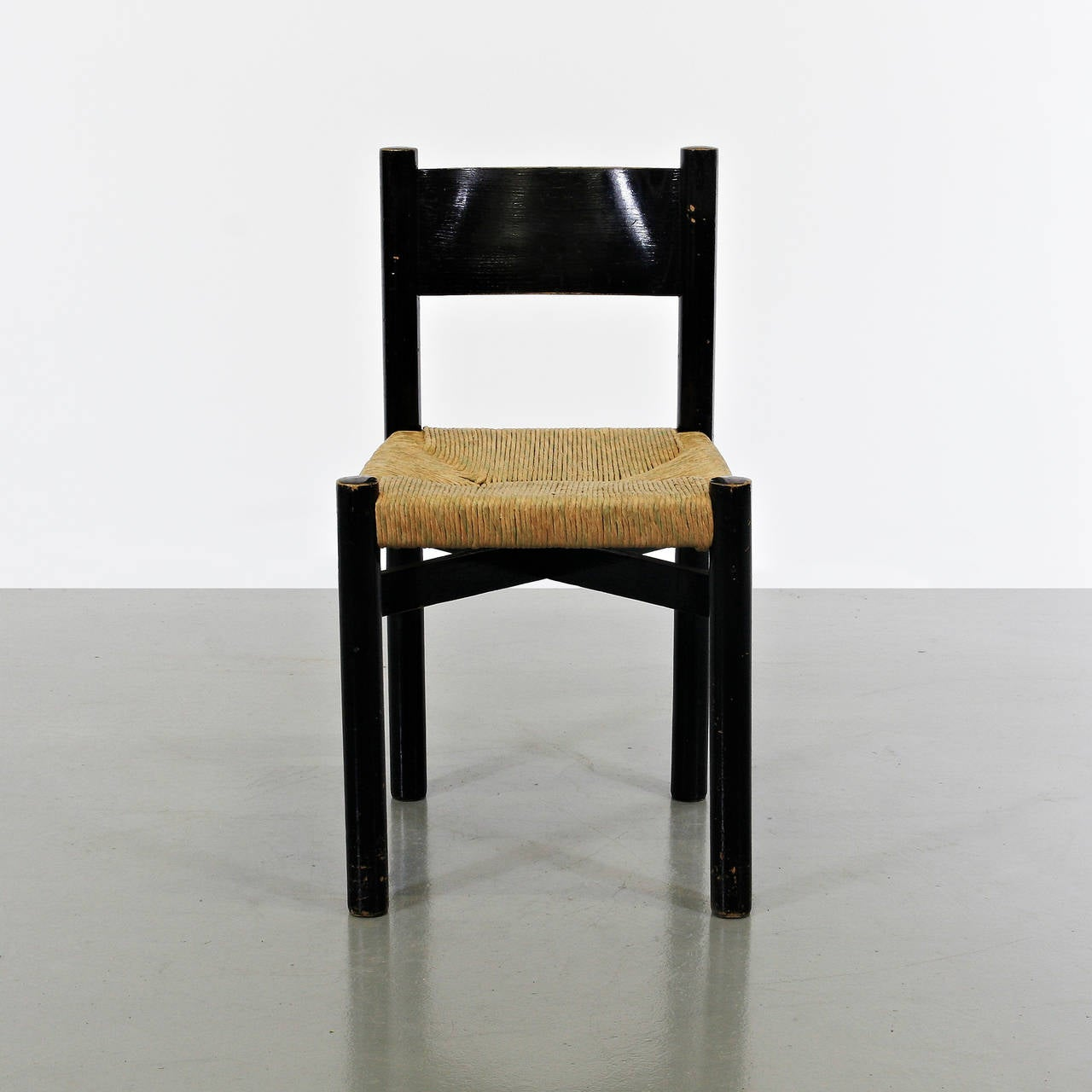 Dining chair, model Meribel, designed by Charlotte Perriand, circa 1950. Manufactured by Georges Blanchon (France) Black lacquered wood base and legs, and original rush seat.  In good original condition, with minor wear consistent with age and