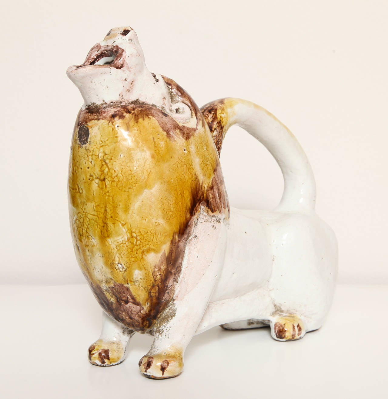 A polychrome painted Italian 1960s pottery lion form pitcher. The charming lion with aubergine and ochre glazed mane. Retaining its original sticker: Made in Italy expressly for Furniture Mart of Miami Inc.