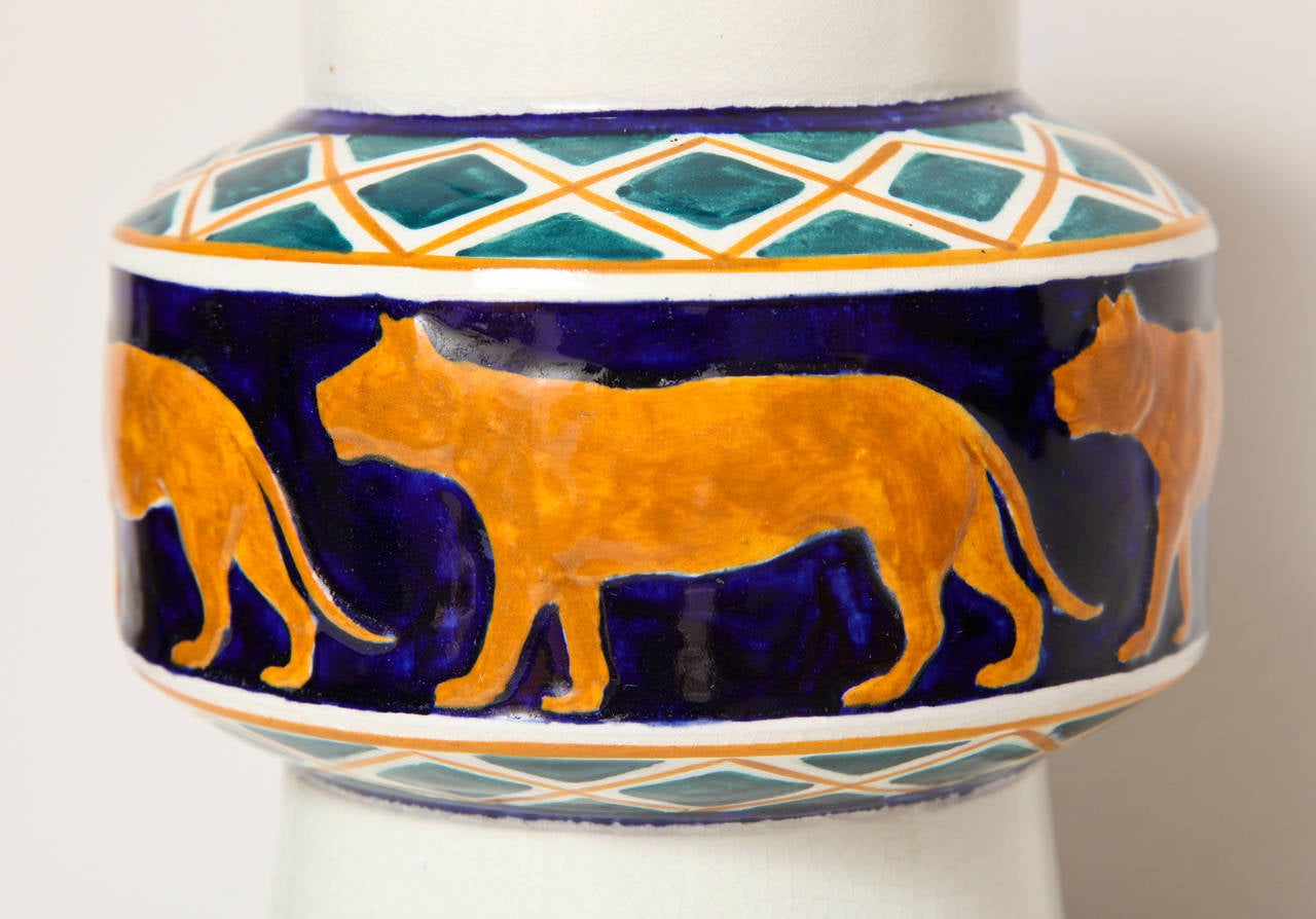 A signed glazed ceramic vase in lapis blue, turquoise and ochre and decorated with a procession of wild animals circling the central band; on a creamy white ground. 