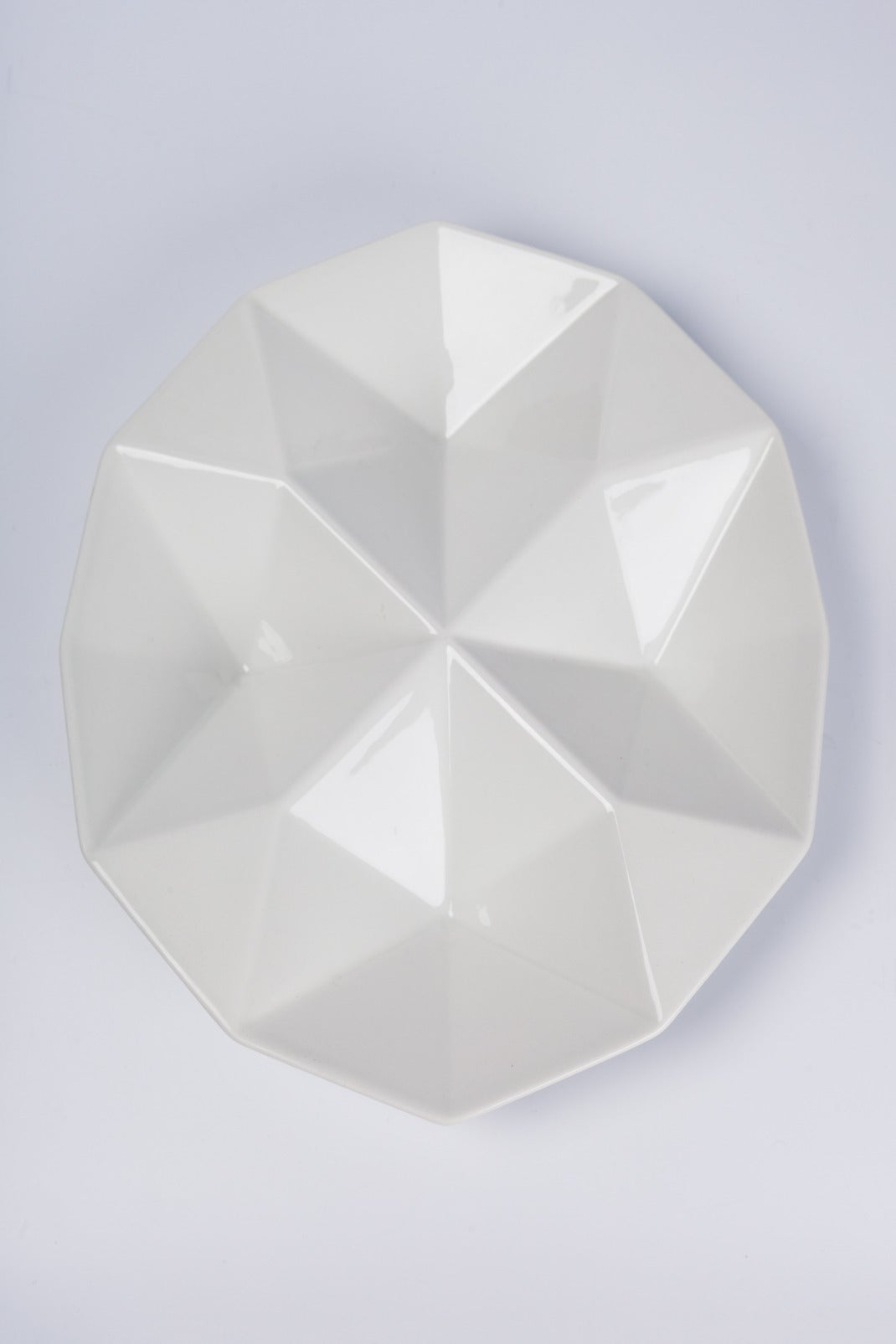 White, oval multifaceted ceramic tray with clear gloss glaze. The geometric pattern like the folds of origami reflects light differently on every facet. Designed in the 1960s by Kaj Franck for Arabia of Finland. Two available.   Kaj Franck (born in