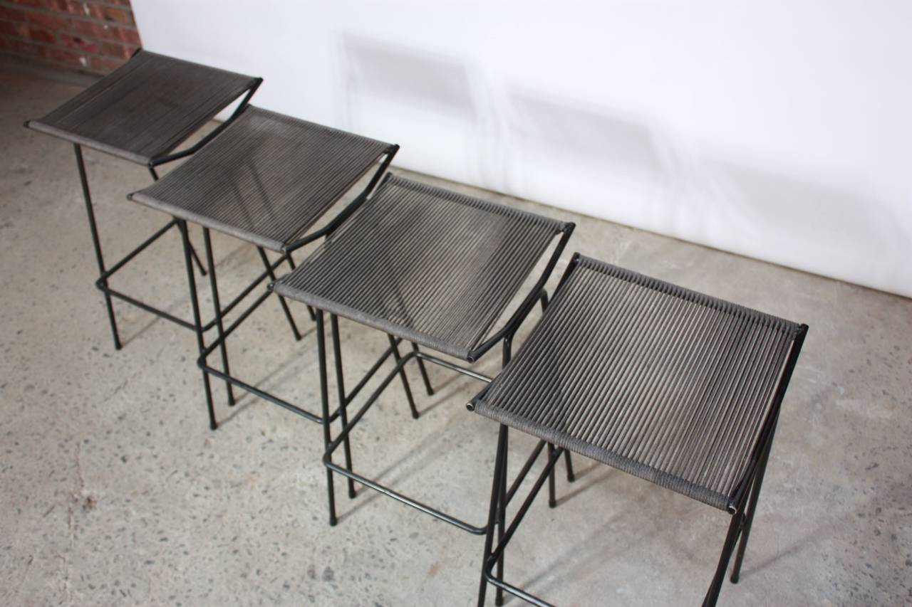 This set of four 1950s Allan Gould iron stools retains their original rope seats. The stools are all in excellent, vintage condition with only age-appropriate, minor wear to the frames and some light fading to the surface of the rope seats.