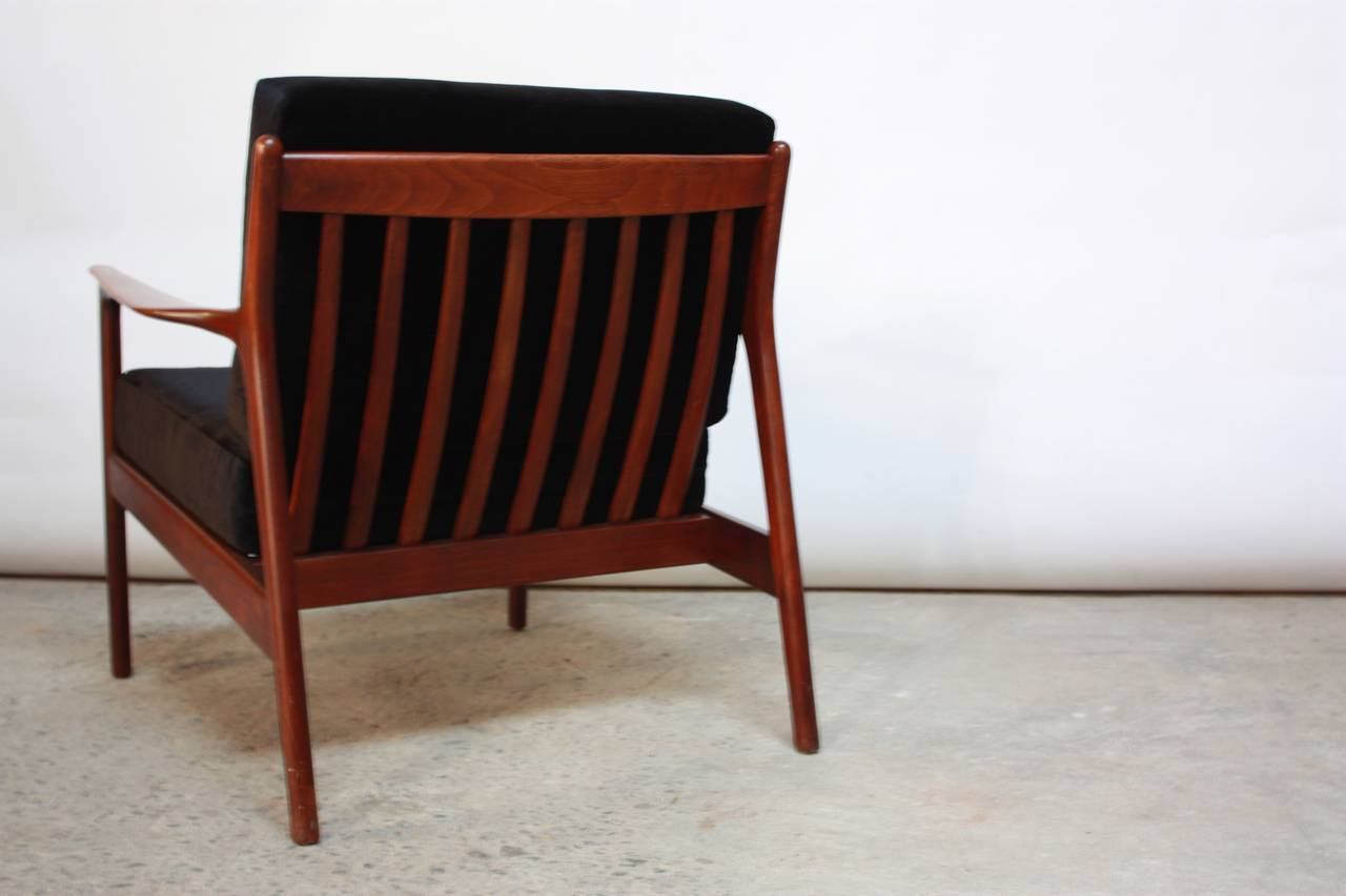 This Danish teak lounge chair is supported by a slat-back and rubber seat straps, which have been newly replaced. The black velvet upholstery is new, as is the foam.