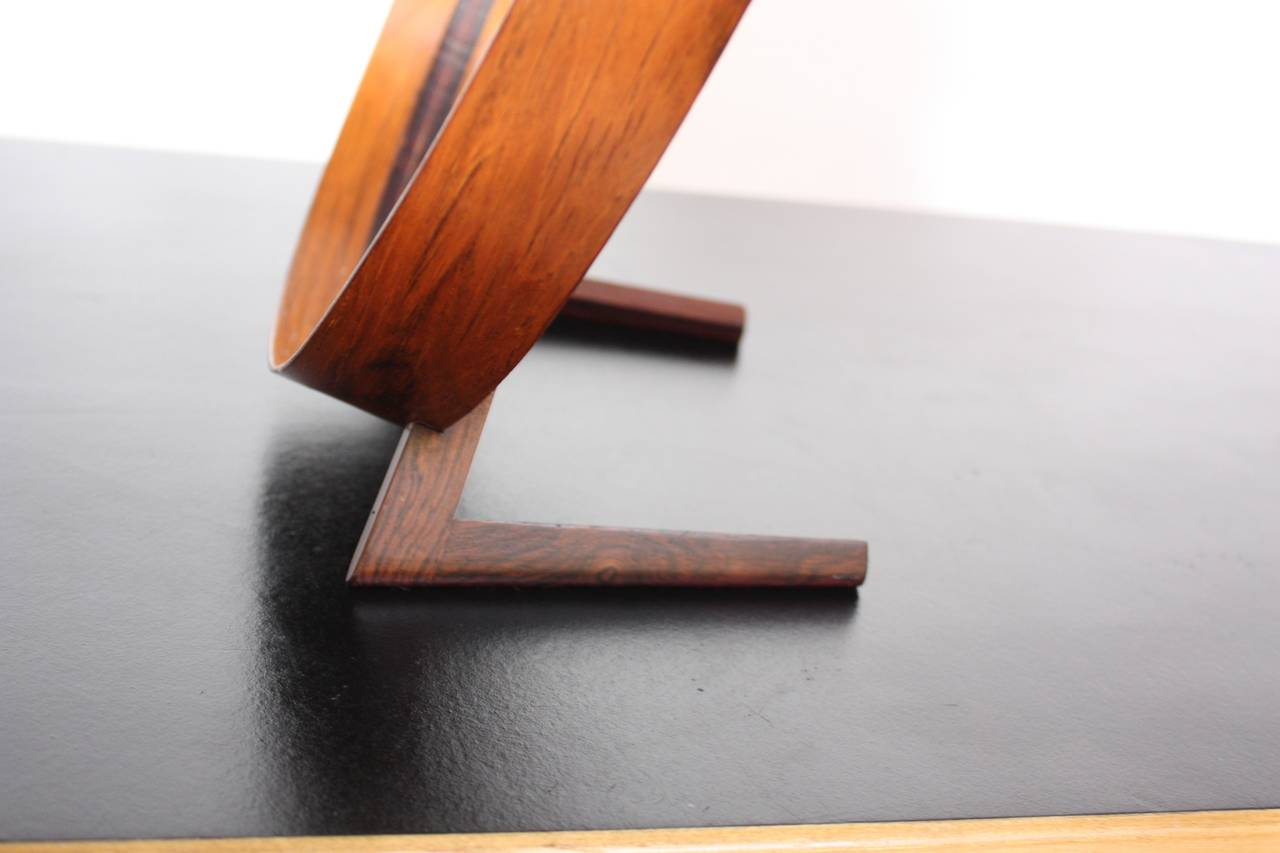This rare rosewood and leather table mirror was designed by Uno and Östen Kristiansson for Luxus. The elegant simplicity of the form is nicely contrasted with the texture and richness of the rosewood.  There is a small spot where the leather has