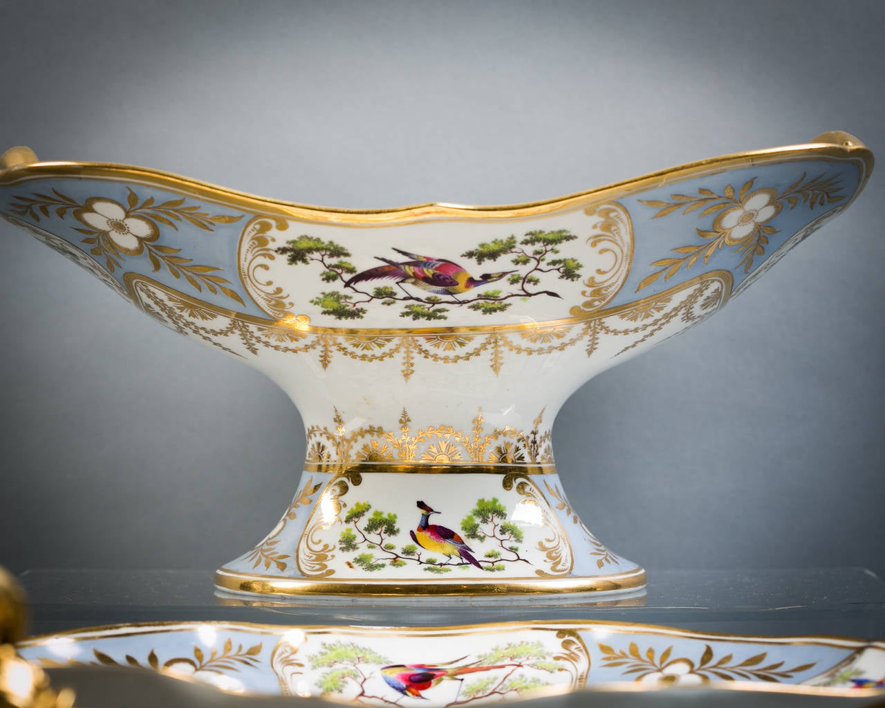 Comprising footed compote, pair of covered sauce tureens, one gallery (partially restored), pair of lozenge-shaped dishes, pair of kidney-shaped dishes, four shell dishes, four square dishes, 12 plates.