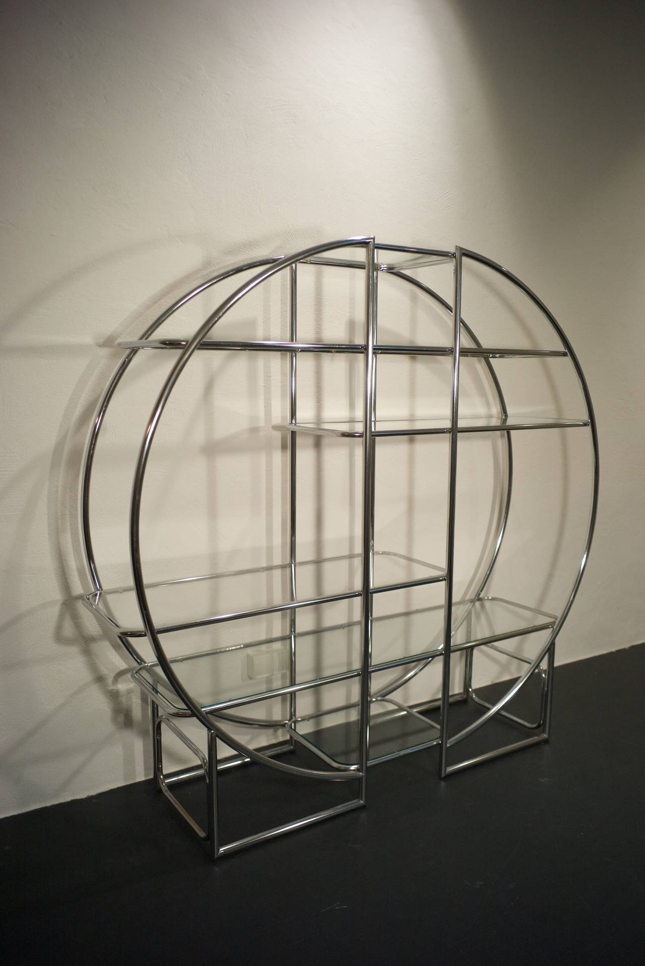 Exceptional circular chrome shelf, which can be placed against a wall, or in the middle of a room, to act as a room divider. It has six glass shelves, all in an excellent condition.