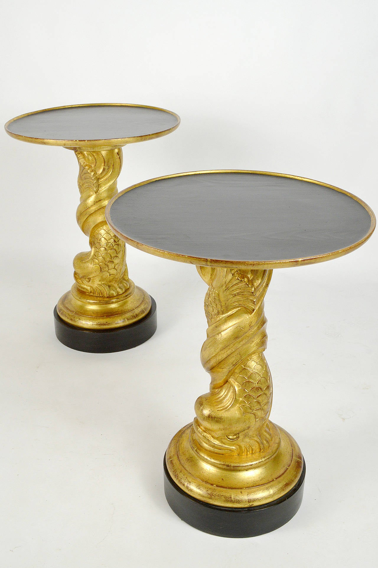 Carved giltwood dolphin side tables, with black lacquered wood top and base, above spiraling dolphin support. Mid-20th century, in the style of James Mont. Hollywood Regency style.
