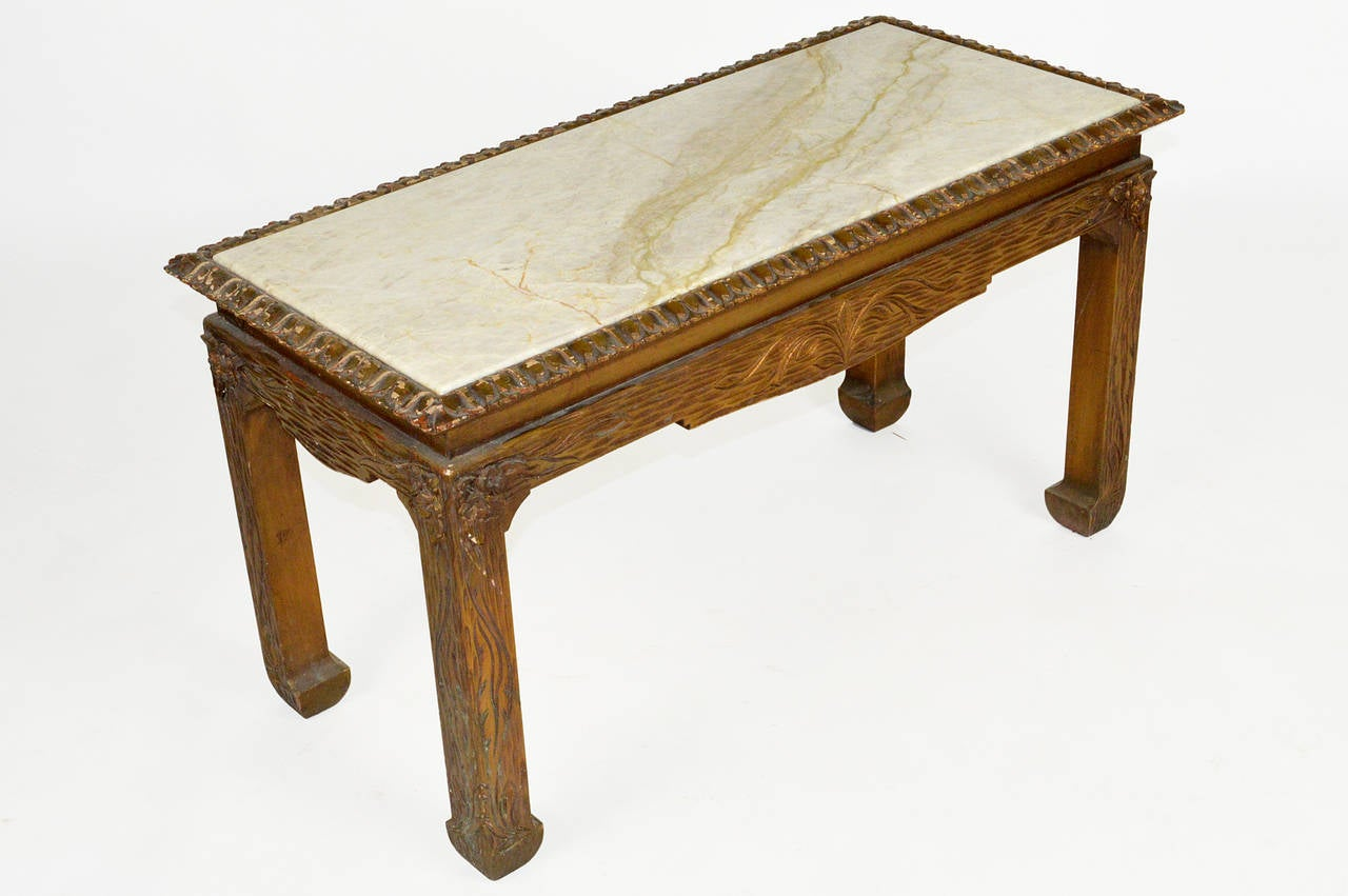 Accent table having a veined marble top inset in frame of distressed painted wood, with carved floral and vine motifs.