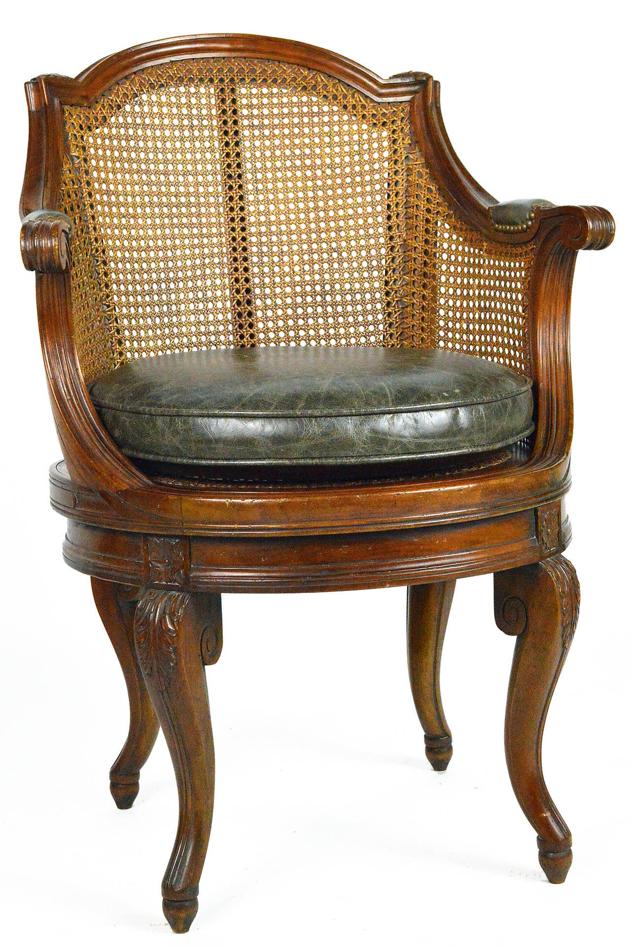 French walnut barrel back swivel armchair having a cane back and seat with acanthus leaf carving to the knee, ending in cabriole legs with leather covered arms and loose leather seat.