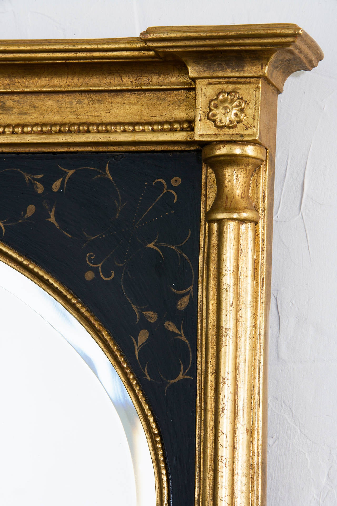 Black and gold mirror with bevel over Mans chest.