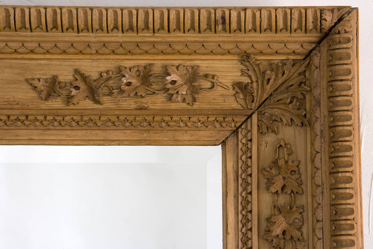 Carved pine frame with beveled mirror. Carved detail as shown. Finish in natural carved pine. Sold as shown. Overall size H 44