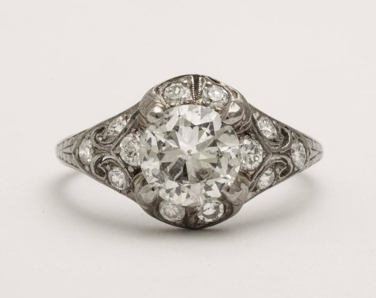 A Classic antique platinum engagement ring with a wonderful centre diamond (1.10 cts) surrounded by smaller diamonds on an elaborately decorated and pierced mount.