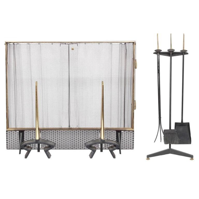 Wrought iron and brass fireplace set (andirons and screen) by  Donald Deskey for Bennett, American, 1950s. The brass has a beautiful patina.  Screen dimensions:  29 inches high x 34 inches wide x 7 inches deep.   Andiron dimensions:  19