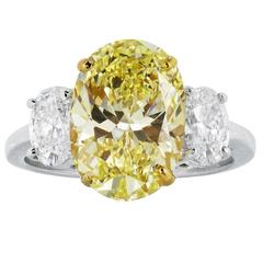 4.55 Carat GIA Cert Oval Shaped Canary Diamond Gold Platinum 3 Stone Ring